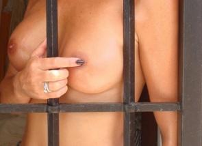 Elle pose seins nus derrière des barreaux