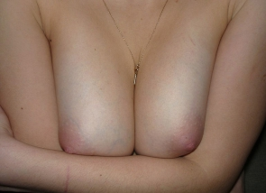 elle sert ses seins entre ses bras